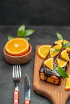 Vertikale ansicht von weichen kuchen an bord und geschnittenen zitronen mit blättern auf dunklem hintergrund