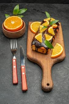 Vertikale ansicht von weichen kuchen an bord und geschnittenen zitronen mit blättern auf dunklem tisch