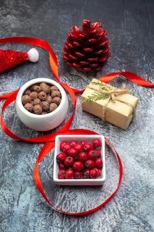 Vertikale ansicht von weihnachtsmann-hut und cornel chocolate red conifer cone geschenk auf dunkler oberfläche
