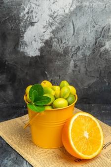 Vertikale ansicht von zitrusfrüchten in einem korb auf zeitung auf grauem hintergrund