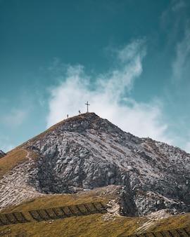 Vertikale ansicht von zwei personen, die nahe dem kreuz auf der spitze eines gipfels klettern