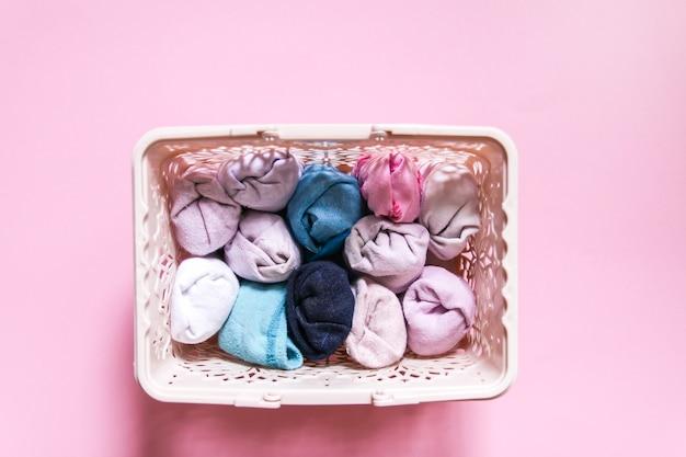 Vertikale aufbewahrung von bunten kleidern in der garderobe. kleidungsstücke in einer schachtel auf weichem rosa hintergrund.
