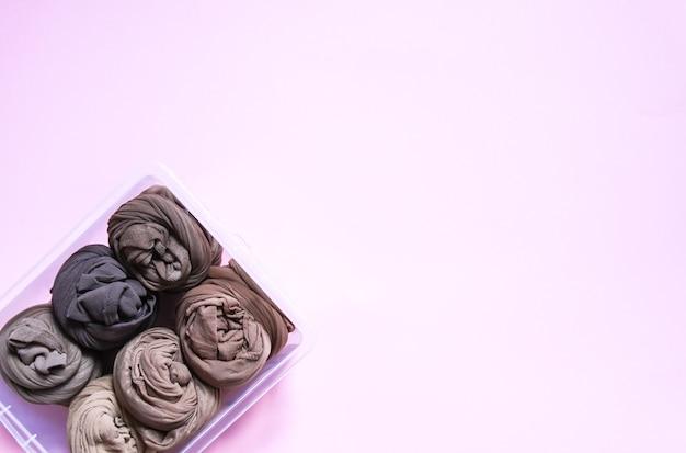 Vertikale aufbewahrung von bunten kleidern in der garderobe. strumpfhosen in einer plastikbox auf weichem rosa hintergrund.
