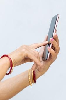 Vertikale aufnahme der faltigen hände einer frau mit einem modernen smartphone