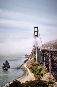 Vertikale aufnahme der golden gate bridge gegen einen nebligen blauen himmel in san francisco, kalifornien, usa