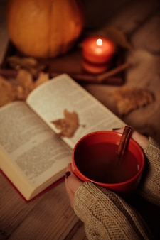 Vertikale aufnahme der hände einer frau, die eine tasse tee auf einem tisch mit einem herbstblatt auf einem buch halten