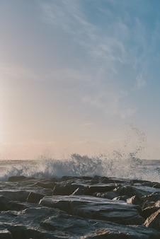 Vertikale aufnahme der meereswellen, die die felsen unter einem blauen himmel treffen