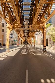Vertikale aufnahme der monorail-brücke über einer straße, aufgenommen an einem sonnigen tag in chicago captured