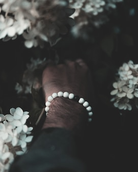 Vertikale aufnahme der nahaufnahme der hand eines mannes mit weißen und schwarzen perlen, die schöne blumen berühren