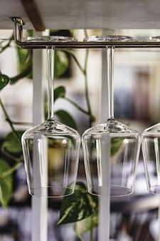 Vertikale aufnahme der nahaufnahme von weingläsern, die an einem gestell hängen