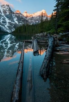 Vertikale aufnahme der schneebedeckten berge, die im moraine lake in kanada reflektiert werden