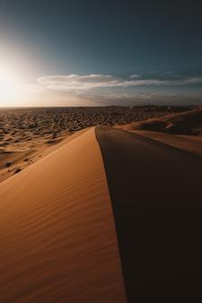 Vertikale aufnahme der schönen wüste unter dem blauen himmel, der in marokko gefangen genommen wird