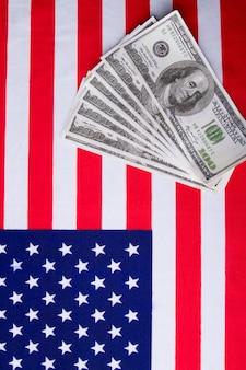Vertikale aufnahme der usa-flagge und dollar-banknoten