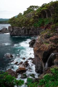 Vertikale aufnahme der wellen des meeres, die auf den klippen krachen