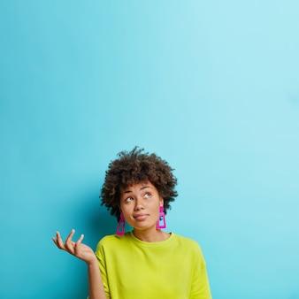Vertikale aufnahme der zweifelhaften afroamerikanischen frau hebt die hand mit zweifel sieht oben verwirrt aus, trifft entscheidung