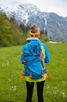 Vertikale aufnahme des aktiven weiblichen reisenden erforscht schönheit der natur, steht gegen berglandschaft