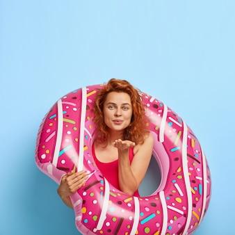 Vertikale aufnahme des attraktiven weiblichen modells sendet luftkuss, gekleidet in badeanzug, steht mit gummidonut, drückt liebe aus, hat sommerferien