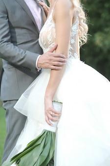 Vertikale aufnahme des bräutigams und der braut, die für ein romantisches hochzeitsfotoshooting posieren