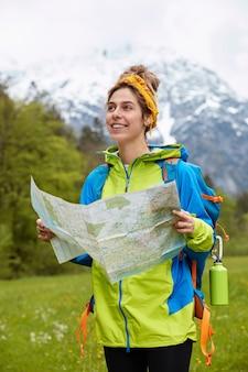 Vertikale aufnahme des erfreuten kaukasischen weiblichen reisenden trägt reisekarte, gekleidet im hellen anorak