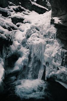 Vertikale aufnahme des gefrorenen wasserfalls, umgeben von felsen im winter