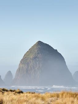 Vertikale aufnahme des haystack rock im morgennebel am cannon beach, oregon