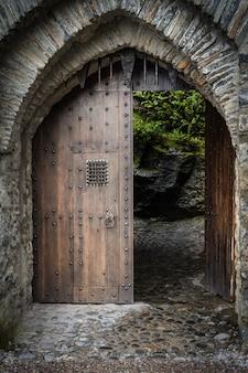 Vertikale aufnahme des holztors am eingang eines schönen historischen schlosses