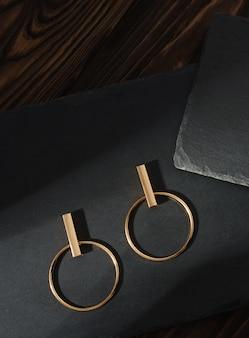 Vertikale aufnahme des modernen goldohrringpaares auf dunklem steinhintergrund auf brauner holzoberfläche