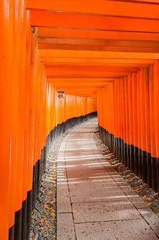 Vertikale aufnahme des orangefarbenen eingangs in den fushimi inari-schrein in kyoto, japan