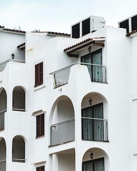 Vertikale aufnahme des weißen gebäudes mit mehreren balkonen