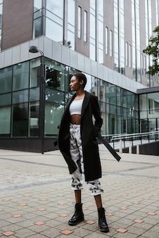 Vertikale aufnahme einer afroamerikanischen frau, die einen mantel trägt, der in der straße aufwirft