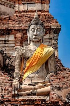 Vertikale aufnahme einer alten buddha-statue, die mit gelbem und orangefarbenem stoff bedeckt ist