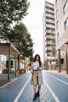 Vertikale aufnahme einer asiatischen jungen frau, die in der straße aufwirft