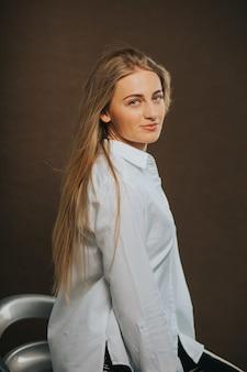 Vertikale aufnahme einer attraktiven blonden frau, die beim sitzen auf einem barhocker aufwirft
