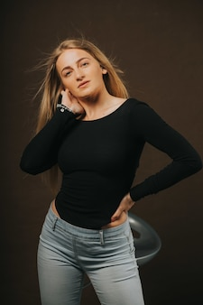 Vertikale aufnahme einer attraktiven blonden frau, die beim sitzen auf einem barhocker posiert