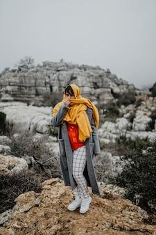 Vertikale aufnahme einer attraktiven jungen frau mit einem mantel und einem roten schal, der auf einer klippe aufwirft