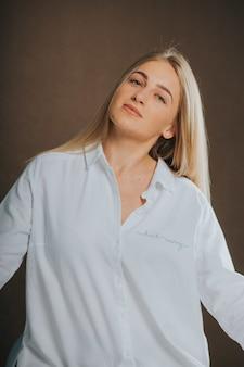 Vertikale aufnahme einer attraktiven kaukasischen blonden frau in einem weißen hemd, die auf einer braunen oberfläche posiert