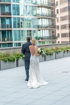 Vertikale aufnahme einer braut und eines bräutigams auf dem schönen balkon, der die gebäude betrachtet