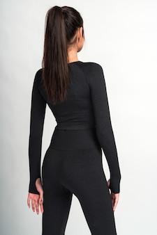 Vertikale aufnahme einer brünetten sportlerin mit langen, schlanken beinen in activewear, die zurück zur kamera steht, während sie drinnen gegen weiße wand posiert