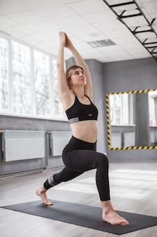 Vertikale aufnahme einer fitten jungen frau, die in krieger-asana steht und im yoga-studio trainiert?