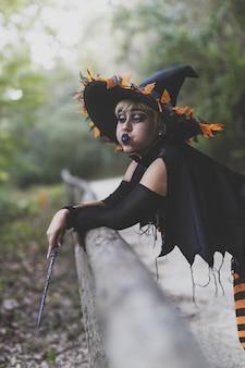 Vertikale aufnahme einer frau, die ein hexen-make-up und ein kostüm mit einem zauberstab trägt, der in einem wald gefangen genommen wird