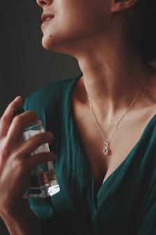 Vertikale aufnahme einer frau, die eine halskette mit einem diamantanhänger trägt, der parfüm auf sie sprüht