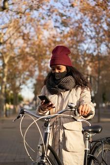 Vertikale aufnahme einer frau, die ihr fahrrad mit ihrem smartphone fährt. sie trägt winterkleidung und ist in einer stadt mit herbstwetter.