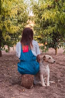 Vertikale aufnahme einer frau, die mit einem hund in einem park mit pfirsichbäumen auf einem baumstamm sitzt