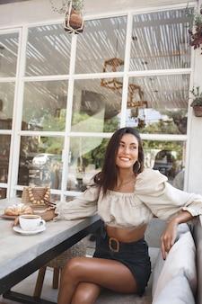 Vertikale aufnahme einer frau im modischen outfit, die cafébereich mit kaffee und croissant sitzt und auf die straße schaut.