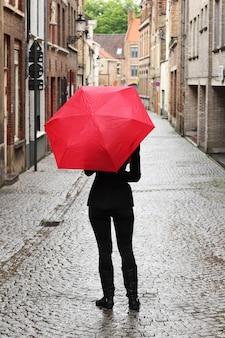 Vertikale aufnahme einer frau mit einem roten regenschirm in der straße