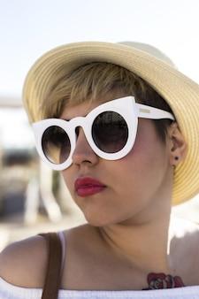 Vertikale aufnahme einer frau mit weißer sonnenbrille und hut am strand