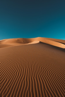 Vertikale aufnahme einer friedlichen wüste unter dem klaren blauen himmel, aufgenommen in marokko