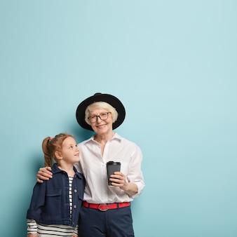 Vertikale aufnahme einer fröhlichen älteren frau umarmt ihre kleine enkelin, gibt ratschläge, trägt modische kleidung