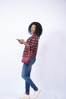 Vertikale aufnahme einer glücklichen jungen afrikanerin, die seitlich geht, während sie ihr telefon benutzt