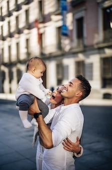 Vertikale aufnahme einer glücklichen kaukasischen familie, die ihr kleinkind hält